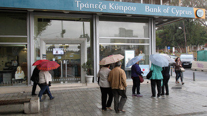 Cypriots walk outside a Bank of Cyprus branch on the island's capital Nicosia (Reuters / Andreas Manolis)