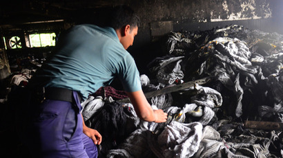 A Bangladeshi police official sifts through burnt clothes inside a gutted garment factory in Dhaka on May 9, 2013 (AFP Photo / Munir uz Zaman)