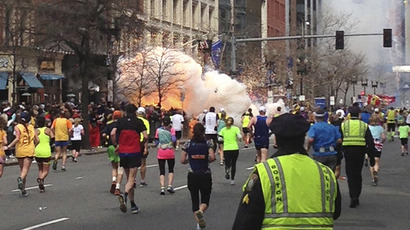Runners continue to run towards the finish line of the Boston Marathon as an explosion erupts near the finish line in Boston, Massachusetts, April 15, 2013. (Reuters / Dan Lampariello)