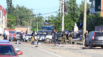Law enforcement officers working at the site where bombs exploded near the bailiff service building in Makhachkala on May 20, 2013. (RIA Novosti / Arsen Abdullayev)