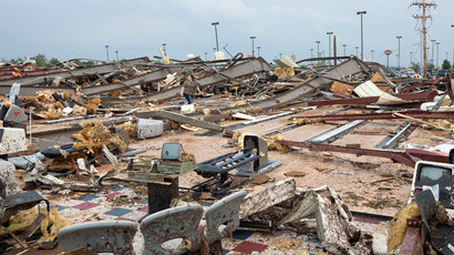 A woman walks through debris after a huge tornado struck Moore, Oklahoma, near Oklahoma City, May 20, 2013 (Reuters / Richard Rowe)