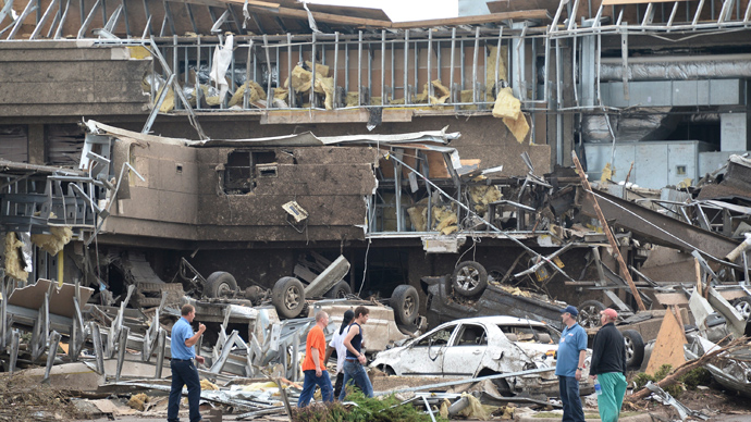 People survey the destructions at the Moore hospital after it was hit by a tornado that destroyed buildings and overturned cars in Moore, Oklahoma, May 20, 2013 (Reuters / Gene Blevins)