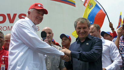 Venezuela's state-owned oil company, president Rafael Ramirez (L) shakes hands with Russia's Rosneft Executive Chairman Igor Sechin (R) during a visit to the JOSE cryogenic plant in Barcelona, Anzoategui state, Venezuela, on May 23, 2013 (AFP Photo / Valeria Pacheco)