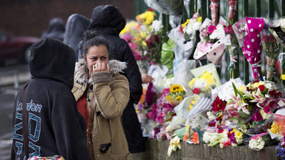 A woman reacts as she looks at floral tributes left at the scene where Drummer Lee Rigby of the 2nd Battalion was killed outside Woolwich Barracks in London on May 24, 2013 (AFP Photo / Justin Tallis)