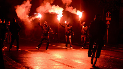 "Members of the Black bloc parade with flares on late May 25, 2013 in the center of Switzerland's capital Bern during the 3rd edition of ""Tanz Dich Frei"" (Dance Yourself Free) a politically-tinged techno parade and mass unauthorised rally (AFP Photo / Fabrice Coffrini)"