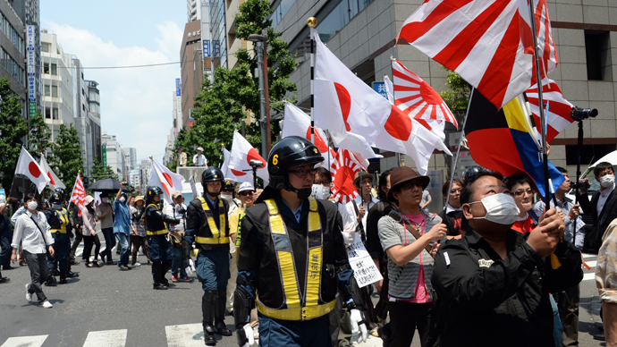 Protected by riot police officers, demonstrators carrying Japanese flags march in a protest against crimes caused by foreign residents in Japan at the Shinjuku shopping district in Tokyo on May 26, 2013 (AFP Photo / Toshifumi Kitamura)