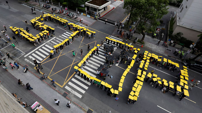"Around 500 residents form the word ""STOP"" with yellow boards atop their heads, outside the Legislative Yuan building during an anti-nuclear protest in Taipei, May 26, 2013.(Reuters / Patrick Lin)"