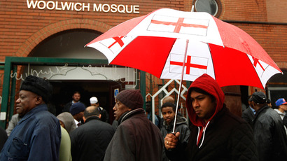 A man with a St George flag umbrella walks among worshippers leaving the Woolwich Mosque after Friday prayers in Woolwich, southeast London May 24, 2013 (Reuters / Luke MacGregor)