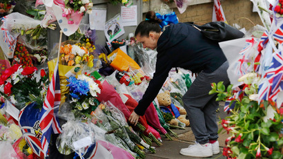 A woman lays flowers alongside floral tributes, flags and balloons left for British soldier Lee Rigby, near the scene where he was killed in Woolwich, southeast London May 28, 2013 (Reuters / Luke MacGregor)