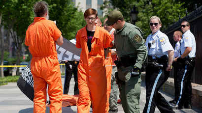 Activists wearing orange jumpsuits are arrested during a protest marking the 100th day of prisoners' hunger strike at Guantanamo Bay in front of the White House in Washington, May 17, 2013 (Reuters / Joshua Roberts)