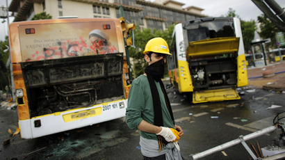 A demonstrator stands in front of a damaged bus in Taksim where police and anti-government protesters clashed in central Istanbul June 2, 2013. (Reuters / Murad Sezer)