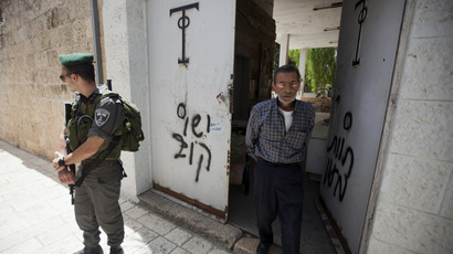 "An Israeli border guard stands next to anti-Christian graffiti reading in Hebrew, ""Jesus is monkey"" that was daubed on the Church of the Dormition, one of Jerusalem's leading pilgrimage sites, on May 31, 2013 (AFP Photo / Ahmad Gharabli)"