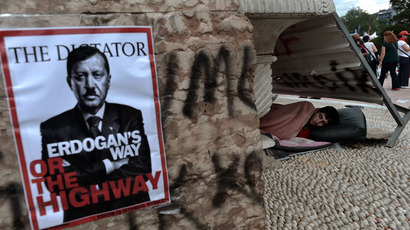 "A man sleeps on Taksim square near a poster showing Turkey's Prime Minister Tayip Erdogan portrayed as ""Hitler"" in Istanbul on June 5, 2013.(AFP Photo / Aris Messinis)"