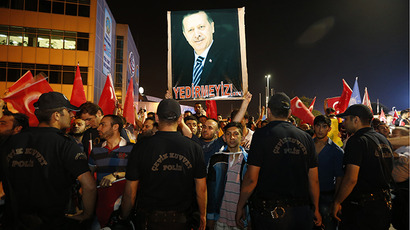 A supporter of Turkish Prime Minister Tayyip Erdogan holds his picture while others shout slogans as they wait for Erdogan's return at Istanbul's Ataturk airport June 6, 2013. (Reuters / Osman Orsal)