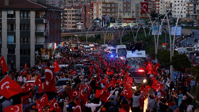 Supporters of Turkey's Prime Minister Tayyip Erdogan wave flags, hold banners and shout slogans as they surround the bus carrying him, his family members and ministers from the airport to the city center in Ankara June 9, 2013.(Reuters / Umit Bektas)
