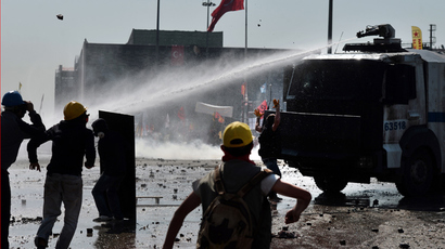 Protesters shield themselves from a water canon during clashes with riot police in Istanbul's Taksim square on June 11, 2013 (AFP Photo / Aris Messinis)