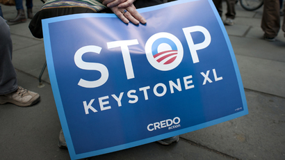 An environmental activist holds a sign in Bryant Park, protesting the proposed Keystone XL pipeline, May 13, 2013 in New York. (AFP Photo / Don Emmert)