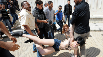 A file picture taken on May 29, 2013 shows two of three topless activists from the Femen feminist group, being arrested as they demonstrate in front of the justice Palace in Tunis (AFP Photo / Fethi Belaid)