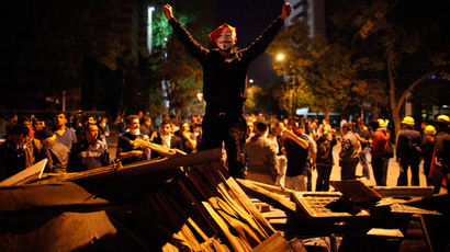 An anti-government protester, wearing a Guy Fawkes mask, gestures while standing on a barricade during a protest in Kennedy street in central Ankara June 12, 2013 (Reuters / Dado Ruvic)