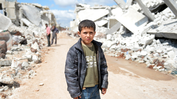 A young Syrian boy poses for a picture between destroyed houses in the northern Syrian town of Azaz (AFP Photo)