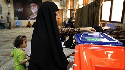 An Iranian woman casts her vote in the presidential election at a polling station in Tehran on June 14, 2013. (AFP Photo / Atta Kenare)