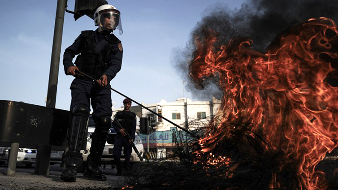 A Bahraini policeman extinguishes tyres burning during clashes with riot police following a protest in solidarity with jailed Bahraini women in the village of Jidhafs, west of Manama, on June 13, 2013. (AFP Photo / Mohammed Al-Shaikh)