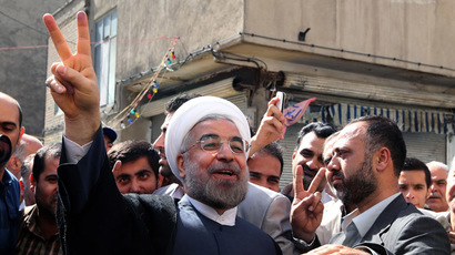 Iranian moderate presidential candidate, Hassan Rohani (C) flashes the sign of victory as he leaves a polling station after voting on in Tehran during the first round of the presidential candidate.  (AFP Photo)
