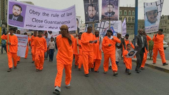 Relatives of Yemeni prisoners being held at the US-run Guantanamo Bay detention camp march in orange jumpsuits while holding their pictures during a demonstration calling for their release outside the US embassy in Sanaa on June 17, 2013. (AFP Photo / Gamal Noman)