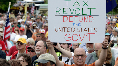 "A man holds up a placard during a Tea Party rally to ""Audit the IRS"" in front of the U.S. Capitol in Washington June 19, 2013 (Reuters / Gary Cameron)"
