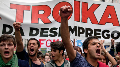 "Demonstrators shout slogans in front of a banner reading ""TROIKA: unemployment"" as they take part in the May Day protest rally in downtown Lisbon (AFP Photo)"
