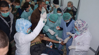 In this image made available by the Syrian News Agency (SANA) on March 19, 2013, medics and other masked people attend to a man at a hospital in Khan al-Assal in the northern Aleppo province, as Syria's government accused rebel forces of using chemical weapons for the first time. (AFP/SANA)