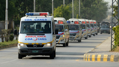 Pakistani police escort ambulances carrying the coffins of foreign tourists as they come out from Chaklala air base in Rawalpindi on June 23, 2013. (AFP Photo / Farooq Naeem)