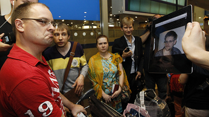 Journalists show an iPad with the picture of Edward Snowden to passengers of a flight from Hong Kong trying to find out if Snowden was aboard the plane, in Moscow's Sheremetyevo airport, June 23, 2013. (Reuters / Sergei Karpukhin)