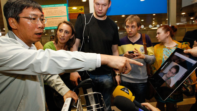 Journalists show an iPad with the picture of Edward Snowden, former contractor for the U.S. National Security Agency, to passengers of a flight from Hong Kong trying to find out if Snowden was aboard the plane, in Moscow's Sheremetyevo airport, June 23, 2013.(Reuters / Sergei Karpukhin)
