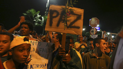 "A demonstrator holds a sign reading ""Peace"" during a protest outside of Rio de Janeiro governor Sergio Cabral's house in Rio de Janeiro June 25, 2013. (Reuters)"