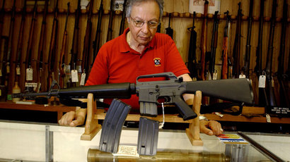 Gun shop manager Stephan Romanoff displays an AR-15 rifle and two magazines.(AFP Photo / Jeff Swensen)