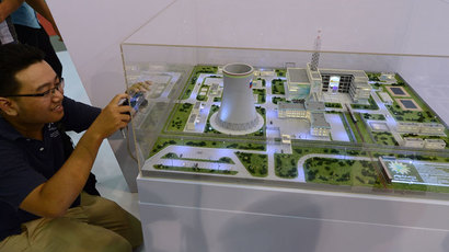 A student takes picture of a model of a Russian nuclear power plant on display at an international nuclear power exhibition being held in Hanoi.( AFP Photo / Hoang Dinh Nam)