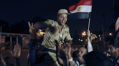 An army soldier (C) cheers with protesters, who are against Egyptian President Mohamed Mursi, as they dance and react in front of the Republican Guard headquarters in Cairo July 3, 2013. (Reuters/Louafi Larbi)
