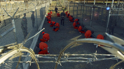 Detainees in orange jumpsuits sit in a holding area under the watchful eyes of military police; January 11, 2002 file photograph (Reuters)