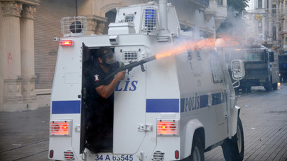 A Turkish riot policeman fires tear gas during clashes with police on Istiklal Avenue in Istanbul on July 6, 2013. (AFP Photo/Bulent Kilic)