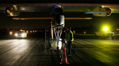 A Solar Impulse crew member walks in front of a sun-powered aircraft at Moffett Field (Reuters / Stephen Lam)