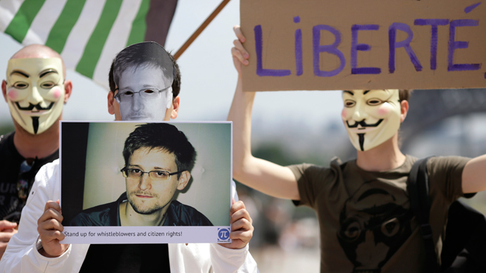 A demonstrator holds up a picture of the former technical contractor of the US Central Intelligence Agency Edward Snowden during a demonstration in support of Snowden at the Place du Trocadero in front of the Eiffel tower in Paris on July 7, 2013 (AFP Photo / Kenzo Tribouillard)