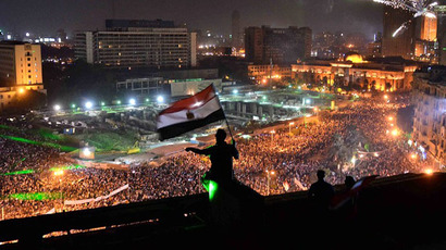 Egyptians wave the national flag on a building rooftop on July 7, 2013 as hundreds of thousands flood Egypt's landmark Tahrir square to demontrate against ousted President Mohammed Morsi. (AFP Photo / Mohamed El-Shahed)