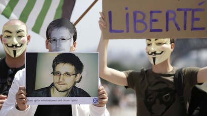 A demonstrator holds up a picture of the former technical contractor of the US Central Intelligence Agency Edward Snowden during a demonstration in support of Snowden at the Place du Trocadero in front of the Eiffel tower in Paris on July 7, 2013. (AFP Photo/Kenzo Tribouillard)