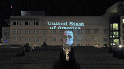 "This handout picture released on July 9, 2013 and taken during the night to July 8, 2013 shows the face of Megaupload founder Kim Schmitz also known as Kim Dotcom and the lettering ""United Stasi of America"" being displayed on the facade of the US embassy in Berlin (on L can be seen the cupola of the Reichstag building housing the Bundestag, lower house of parliament). (AFP Photo)"