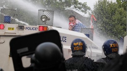 An Orangemen protester stands on a police vehicle as police use water cannon during clashes on the return from a march in north Belfast, Northern Ireland, on July 12, 2013 (AFP Photo / Peter Muhly)