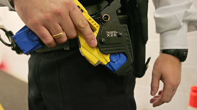 A British police officer holsters a taser gun (AFP Photo / Carl de Souza)
