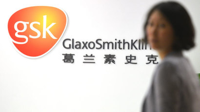 An employee of British drug firm GlaxoSmithKline (GSK) enters their office headquarters in Shanghai on July 1, 2013.(AFP Photo / Peter Parks)