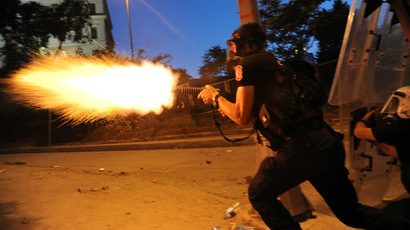 Turkish riot police officer fires tear gas during clashes with protestors between Taksim and Besiktas in Istanbul on June 3, 2013 during a demonstration against the demolition of the park. (AFP Photo/Bulent Kilic)