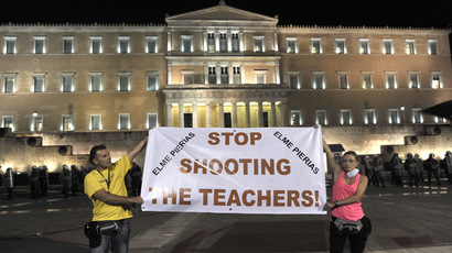 Demostrators hold a banner in front of the parliament during a protest as lawmakers prepared to vote late July 17, 2013 on a controversial new austerity package involving a huge shake-up of the civil service with thousands of jobs on the line. (AFP Photo/Aris Messinis)